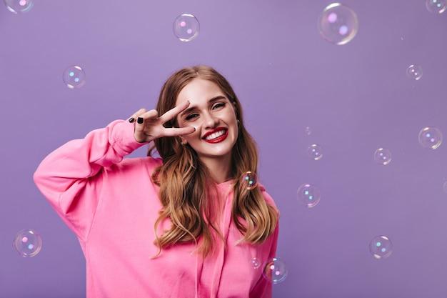 Ragazza allegra in felpa con cappuccio rosa che mostra segno di pace sul muro viola con bolle