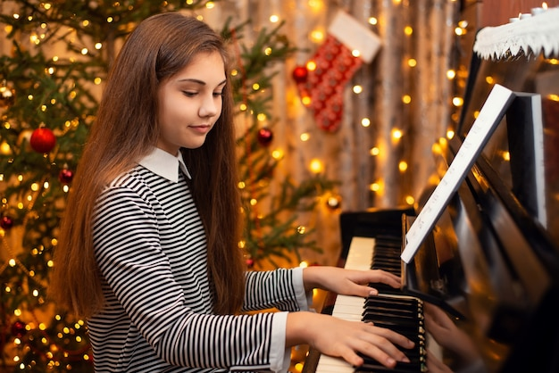 Cheerful girl playing the piano with decorated christmas tree on the background