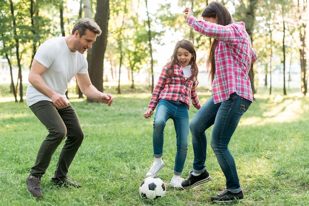 Cheerful girl playing soccer ball with her parent on grass in park