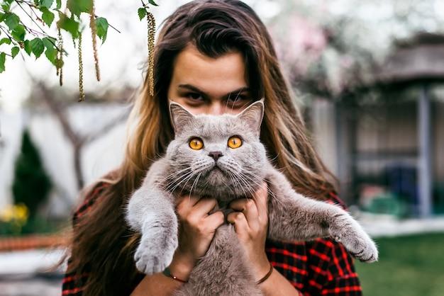 명랑 소녀 봄에 집 마당에 그녀의 고양이와 함께 재생