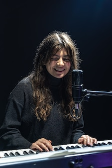 Cheerful girl in the process of recording musical content in the studio, recording voice into a professional microphone, the concept of learning piano online.
