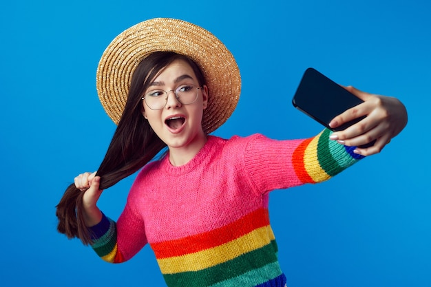 Веселая девушка тянет за длинные волосы, делая селфи со смартфоном