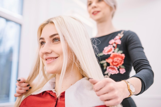 Cheerful girl in salon of hairdresser