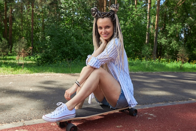 Cheerful girl in short shorts and with dreadlocks sits on a longboard on the road near the park high quality photo