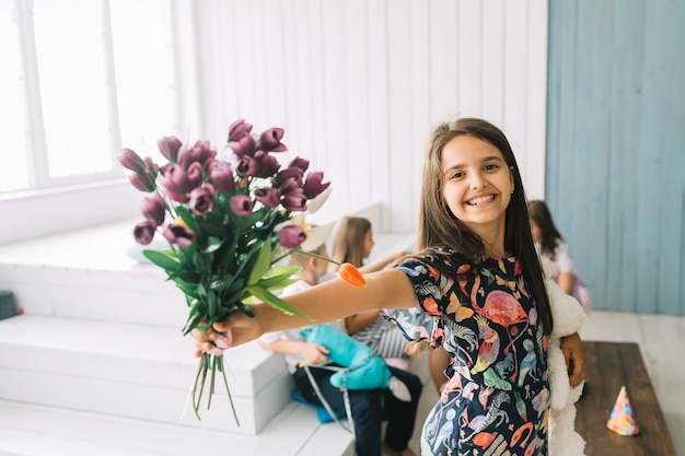 Cheerful girl showing bouquet on birthday party