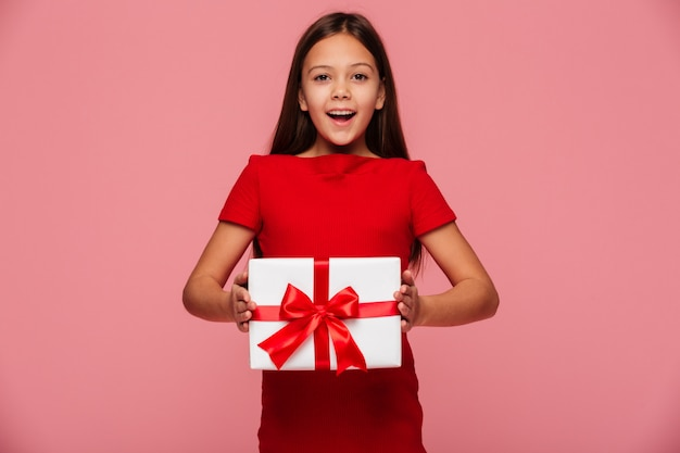 Cheerful girl showing gift and smiling isolated over pink
