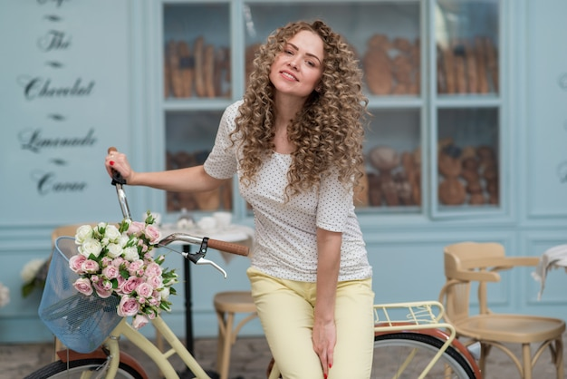 Cheerful girl sits on the bicycle outdoor and looking at the camera wearing