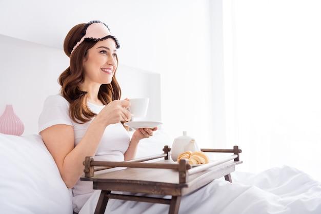 Веселая девушка сидит в постели и ест обед