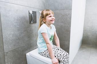 Cheerful girl sitting on toilet