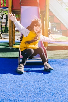 Cheerful girl sliding down on playground