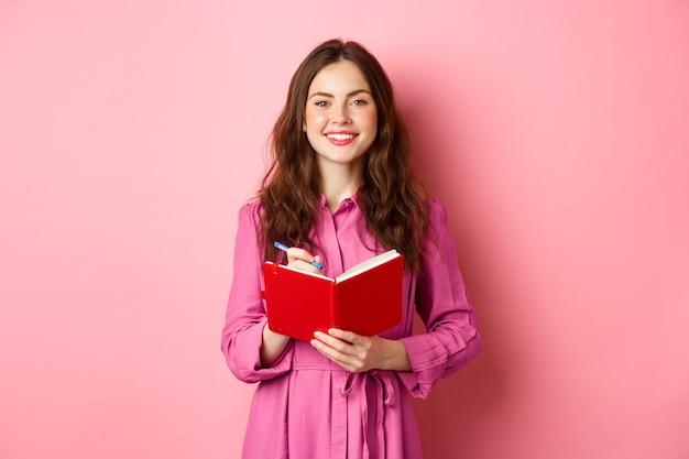 웃 고 메모를 작성, 그녀의 플래너, 계획 일정 또는 식료품 목록을 들고 명랑 소녀 핑크 벽에 일기와 함께 서.