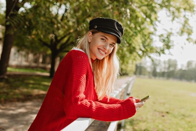 Ragazza allegra che sorride magnificamente divertendosi nel parco. attraente bionda che indossa bei vestiti di stagione rossi.