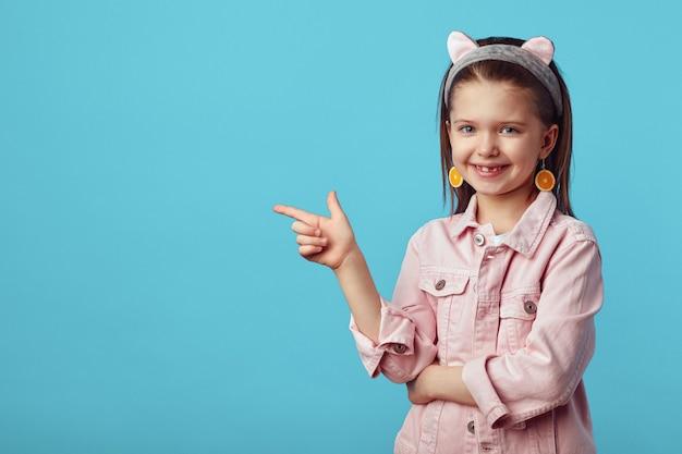 Веселая девушка улыбается, указывая на пустое пространство на синем фоне