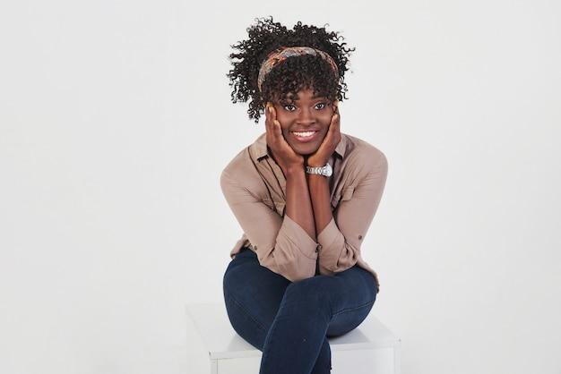 白い背景とスタジオの椅子に座っている笑顔の陽気な女の子