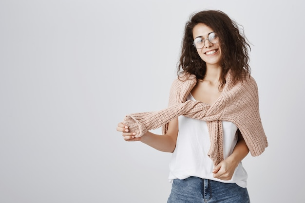 Веселая девушка улыбается, обернуть свитер вокруг плеч