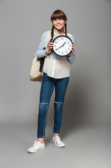 Cheerful girl standing with clock