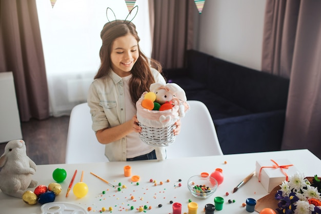 Cheerful girl stands at table in room