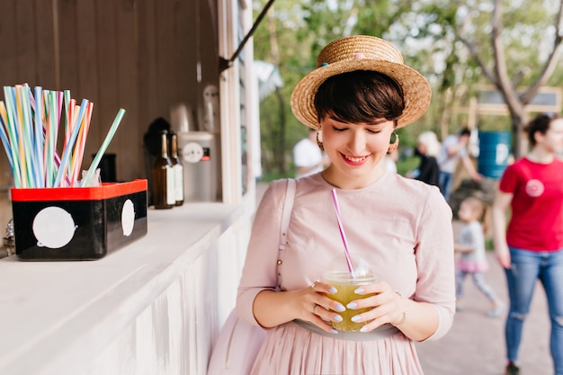 Cheerful girl in straw hat bought a cold drink, walking along the city square
