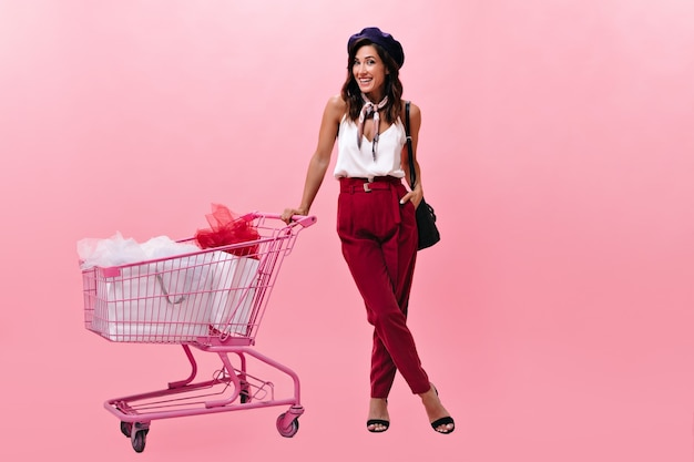 Cheerful girl in stylish pants posing with trolley after shopping. woman in fashionable bright clothes in beret and with handbag smiles at camera.