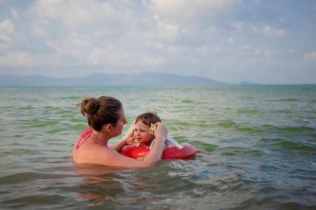 바다에서 엄마와 함께 수영하는..