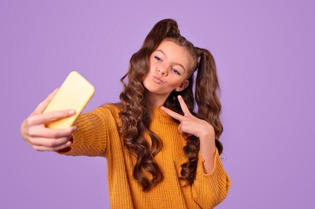 Cheerful girl taking selfie on smartphone