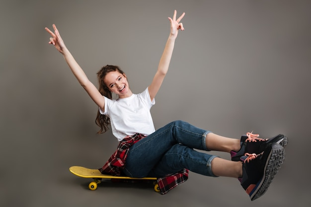 Cheerful girl teenager sitting on skateboard and showing peace sign