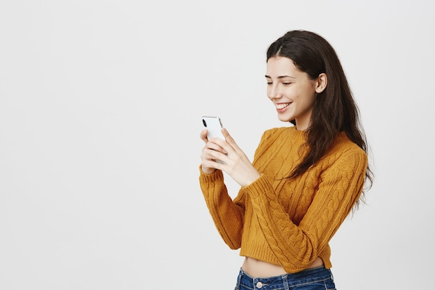 Cheerful girl texting in dating app, looking at smartphone with happy smile