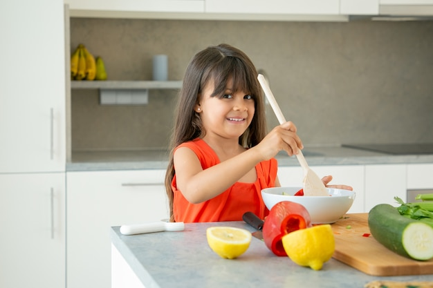 Cheerful girl tossing salad in bowl with big wooden spoon. cute child spending time at home during pandemic, cooking vegetables, posing, smiling at camera. learning to cook concept