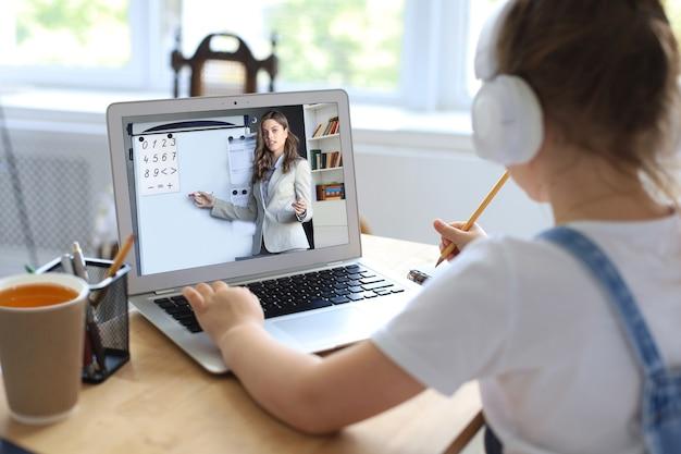 オンラインeラーニングシステムを介して勉強しているラップトップコンピューターを使用して陽気な女の子
