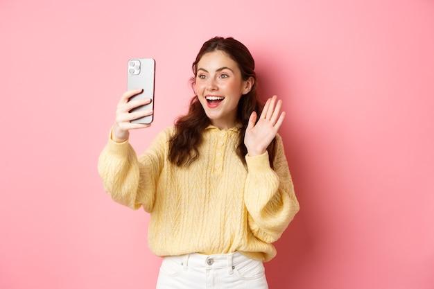 Веселая девушка в видео-чате на смартфоне, машет рукой на камеру телефона и улыбается счастливым, здоровается, стоя у розовой стены.