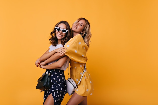 Ragazza allegra in occhiali da sole bianchi vintage godendo il tempo libero con un amico. donne glamour ben vestite che si abbracciano sul giallo.