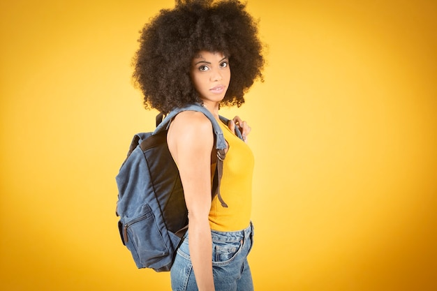 Cheerful girl walking with backpack and camera, mixed afro ameriacana, beautiful happy