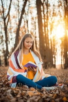 가을 공원에서 따뜻한 격자 무늬로 덮인 주황색 스웨터를 입은 쾌활한 소녀
