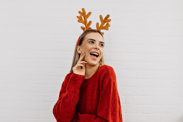 Cheerful girl wears christmas headgear smiling and having fun over isolated background. studio photo of woman red sweater.
