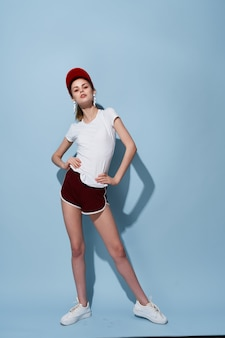 Cheerful girl in white tshirt and shorts posing fashion full length fun