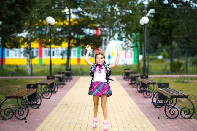 학교 운동장에서 배낭과 교복을 입은 쾌활한 소녀. 학교로 돌아가다