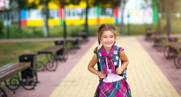 バックパックと校庭の制服を着た陽気な女の子。学校に戻る