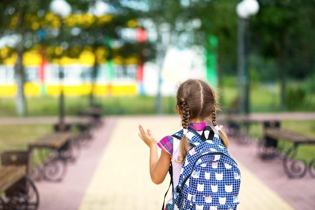 バックパックを背負って、校庭の制服を着た元気な女の子がフレームに戻ります。