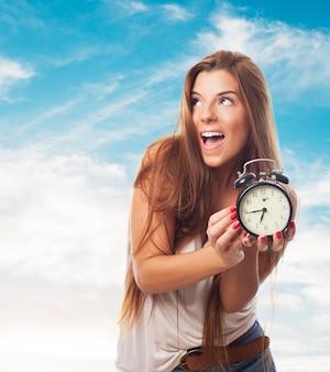 Cheerful girl with alarm clock