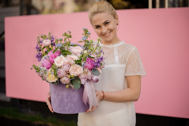 Cheerful girl with bouquet with peonies in box