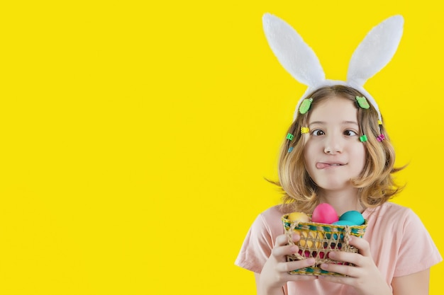 그녀의 손에있는 다채로운 계란 바구니와 함께 그녀의 머리에 재미있는 얼굴과 토끼 귀를 가진 명랑 소녀. 부활절