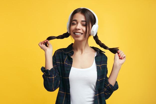 Веселая девушка в наушниках наслаждается звуком музыки, держит свои конские хвосты с закрытыми глазами над желтой стеной