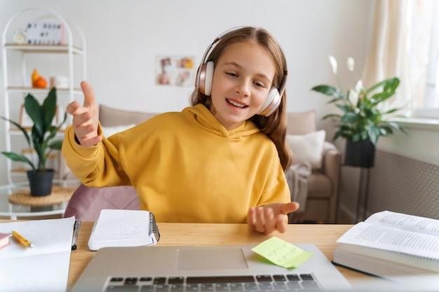 Веселая девушка с наушниками сидит в своей комнате, разговаривает на камеру, имеет видеозвонок, используя портативный компьютер для общения с другом