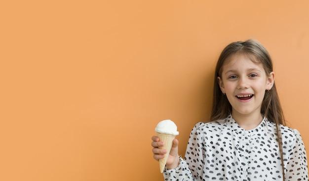 コピースペースとオレンジ色の背景に円錐形のアイスクリームと陽気な女の子。バナーフォーマット