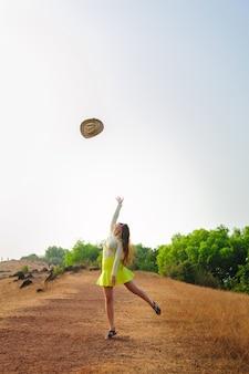 Жизнерадостная девушка с длинными волосами прыгает и бросает соломенную шляпу в воздух. молодая брюнетка женщина в короткой юбке ходит на холме и подбрасывает ее шляпу. концепция активного образа жизни и путешествий