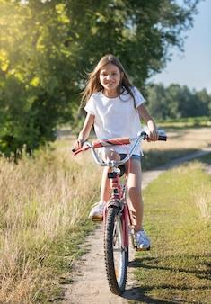 초원에서 비포장도로에서 자전거를 타는 긴 머리를 가진 쾌활한 소녀