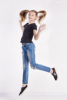 Cheerful girl with long pigtails posing jump