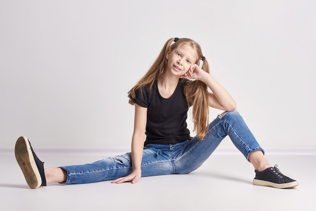 Cheerful girl with long pigtails posing