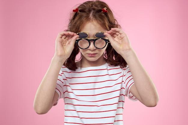 Жизнерадостная девушка с косичками солнцезащитные очки полосатую футболку образ жизни розовый фон.