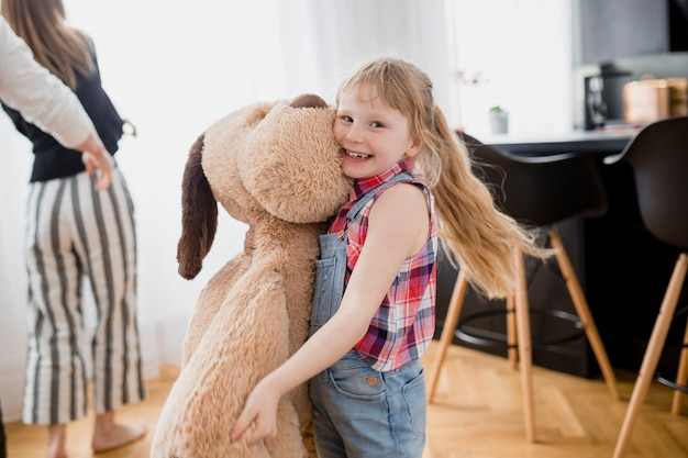 Cheerful girl with plush dog